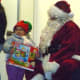 Santa giving a young Port Chester girl a present at last year's holiday kickoff event.